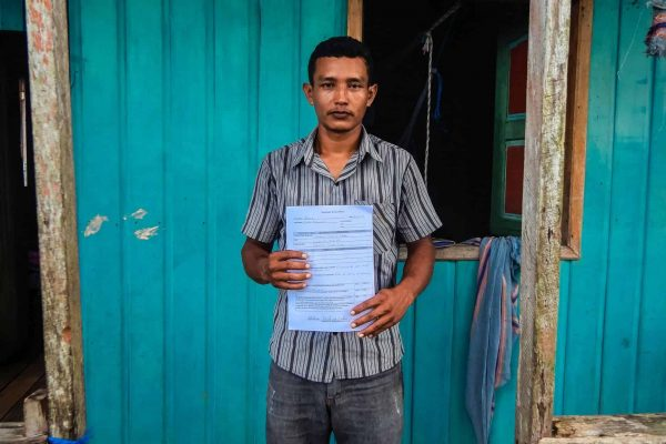 A man shows his tenure documentation, in the Amazon Forest project, Para, Brazil.