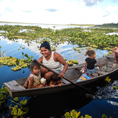 A resident family of the Brazilian Rosewood project paddling in a canoe in shallow waters and wetlands.