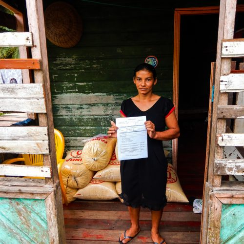 A female resident of the Brazilian Rosewood project holding a certificate of land tenure.