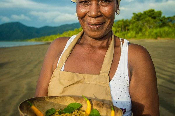 A woman with produce in the Pacific Forest Communities, Colombia.