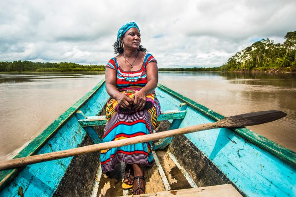 A community member in traditional dress sits in a boat in the Pacific Forest Communities project.