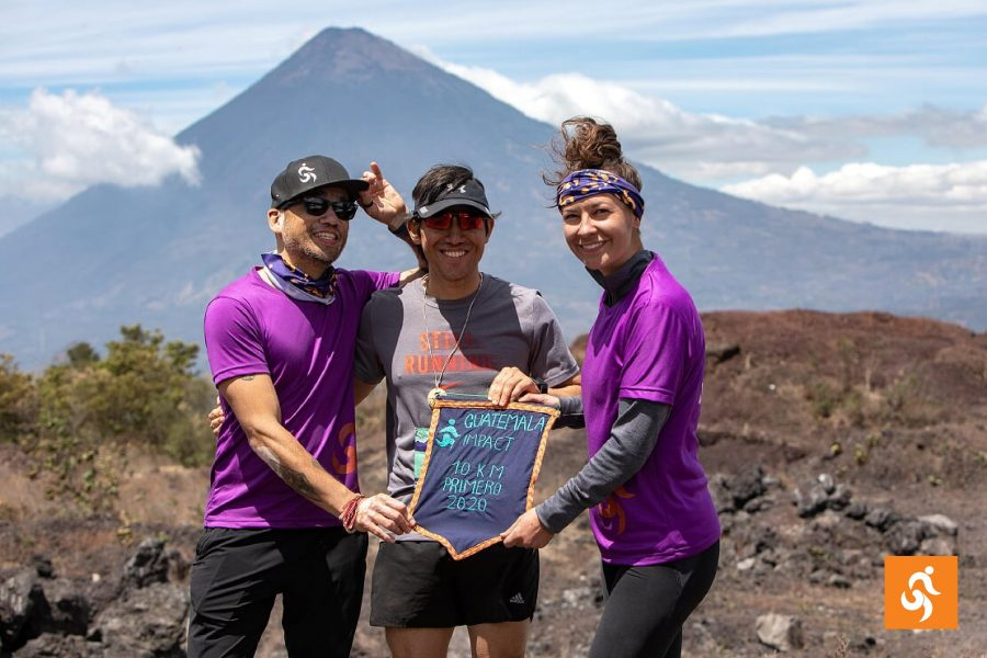 Three Impact Marathon runners in front of a volcano in Guatemala
