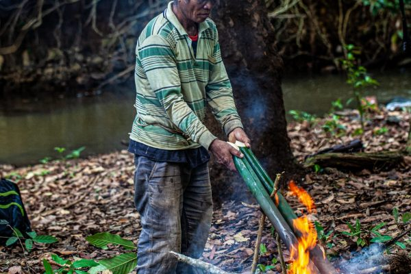 A member of the indigenous Bunung people cooking over an open fire in the Keo Seima project, Cambodia.