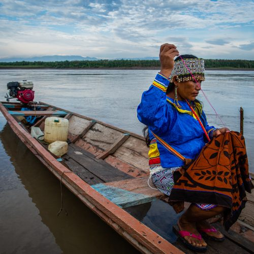 A woman working on traditional handicraft on a canoe in Nii Kaniti, Peru.